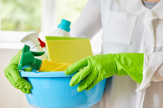 Cleaner with gloves carries cleaning products