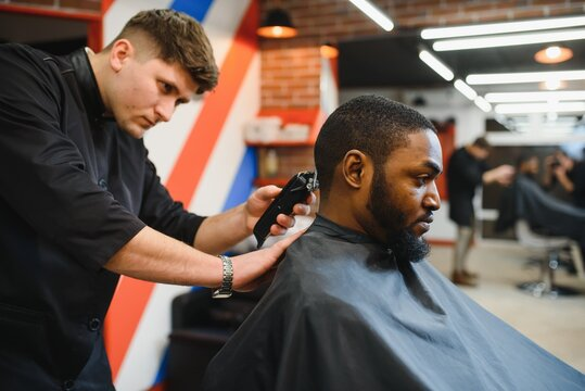 Portrait of young black man being trimmed with professional electric clipper machine in barbershop.Male beauty treatment concept. Young African guy getting new haircut in barber salon