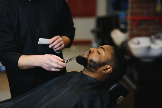 African male client getting haircut at barber shop from professional hairstylist.