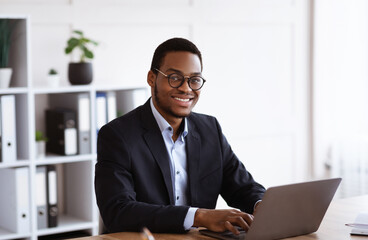 Cheerful african businessman working with laptop in office