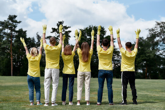 Rear view of happy volunteers wearing yellow uniform and rubber gloves raising hands up, celebrating success after cleaning forest or park together