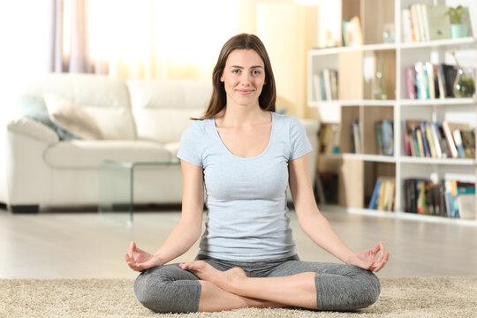 Woman doing yoga at home looking at camera