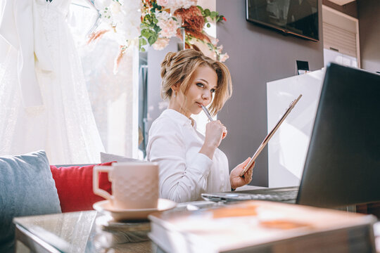 young woman wedding planner in office with laptop and tablet for writing