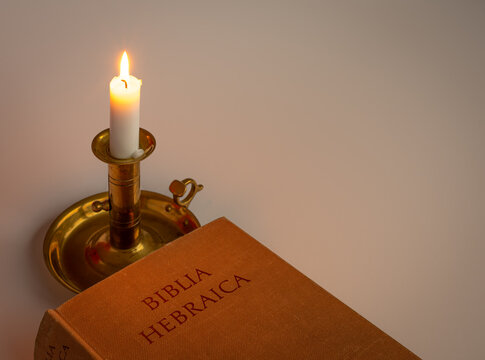 hebrew bible in the light of a candle on a brass stick