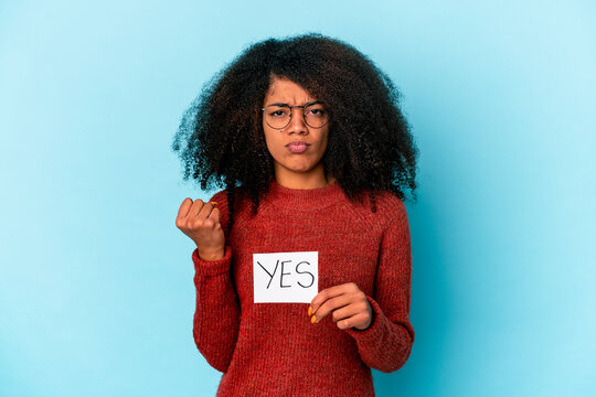 Young african american curly woman holding a yes placard showing fist to camera, aggressive facial expression.