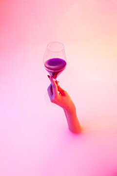 Delicious evening. Close up female hand gesturing from the milk bath with soft white glowing in neon light. Copyspace for advertising. Holding glass of red wine, alcohol. Modern neoned colors.