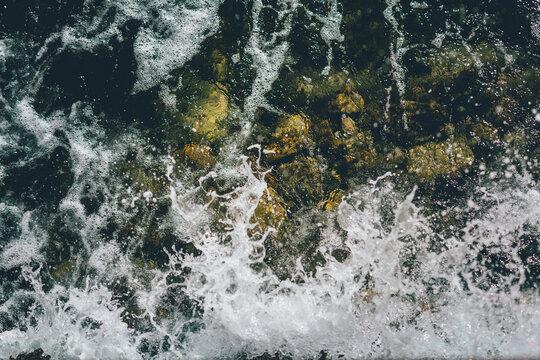 Textura de olas rompiendo en las rocas. Costa. Espuma de mar.
