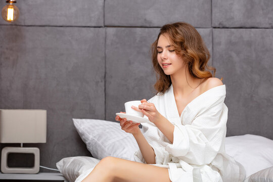Beautiful and sweet young girl in a white coat in the bedroom on the bed fresh and natural with a Cup of coffee in her hands
