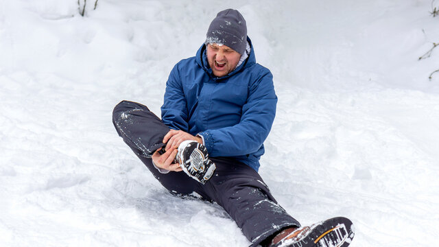 Man having ankle injury while having outdoor activities in cold weather condition. Male climber lying on the snow and touching his injured leg. Young man suffering from pain in leg. Healthcare concept