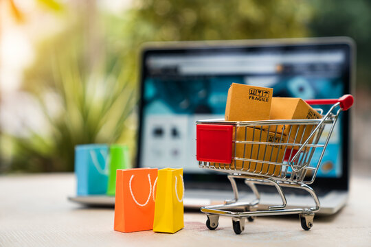 Product package boxes in cart with shopping bag and laptop computer with blurred web store shop on screen for online shopping and delivery concept