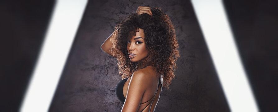 Sexy woman in black bikini posing in front of the camera