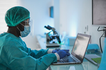 African male doctor working with laptop and protective face mask for coronavirus outbreak - Health...