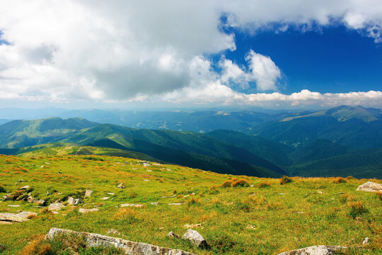 carpathian summer mountain landscape. beautiful countryside with rocks on the grassy hill. view in to the distant valley. clouds on the blue sky. wonderful travel destination