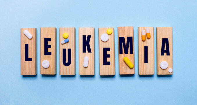The word LEUKEMIA is written on wooden blocks on a light blue table near the pills. Medical concept