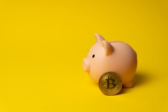 Pink pig as money box on yellow background with BTC coin