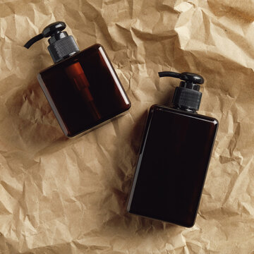 Pump amber glass bottles for soap and shampoo on crumpled paper. Flat lay, top view.