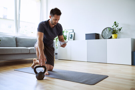 Man setting up online workout app at home