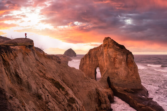 Photographer is taking pictures of the beautiful seaside view on the Oregon Coast. Taken in Cape Kiwanda, Pacific City, during a cloudy winter Sunrise.
