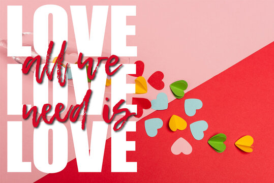 top view of champagne glass with colorful hearts near all we need is love lettering on pink and red
