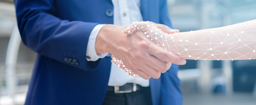 close up on businessman hand shaking with robotic AI hologram to confirm and dealing for business and technology innovation of RPA concept