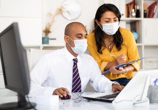 Director in protective medical mask gives instructions to secretary in office