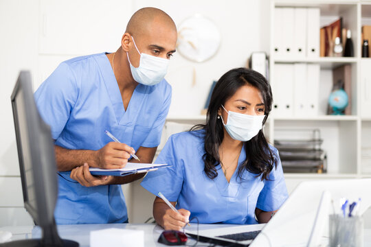 Doctor and nurse in protective medical mask check patient data in hospital computer database