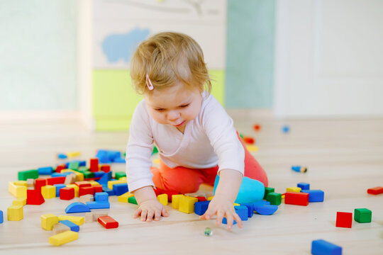 Cute little baby girl playing with educational toys. Happy healthy child having fun with colorful different wooden blocks at home or nursery. Baby crawling and learning colors and forms, indoors