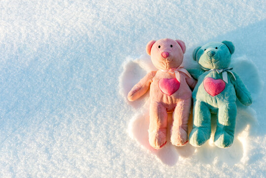 Two small teddy bears are makes a snow angel on a snow.Winter sunny evening.Copy space.