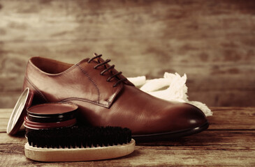 Footwear care accessories and shoe on wooden background