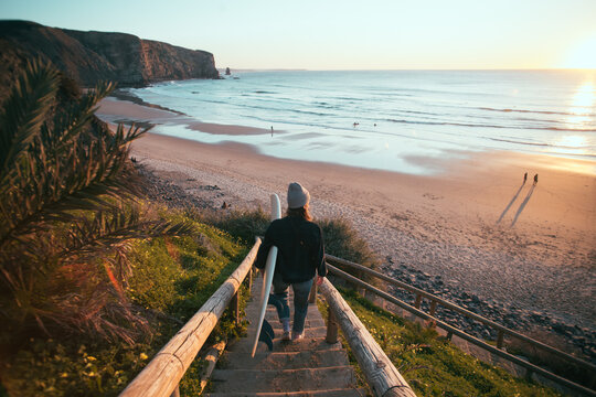 Young woman in casual clothes walk down stairs to beautiful epic beach at sunset or sunrise. Female surfer ready to start surfing lesson at dawn. Millennial lifestyle and hobby