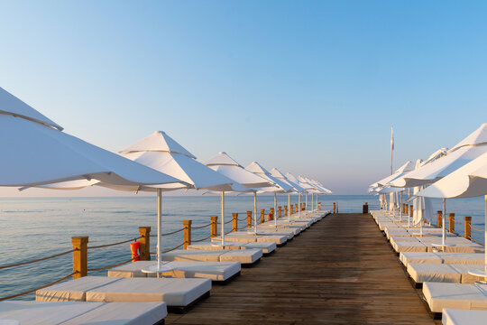 Pier with sunbeds and umbrellas