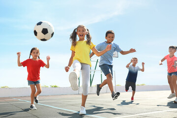 Cute children playing soccer outdoors on sunny day. Summer camp