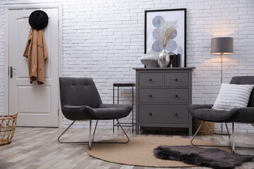 Stylish room interior with grey chest of drawers and chairs near white brick wall