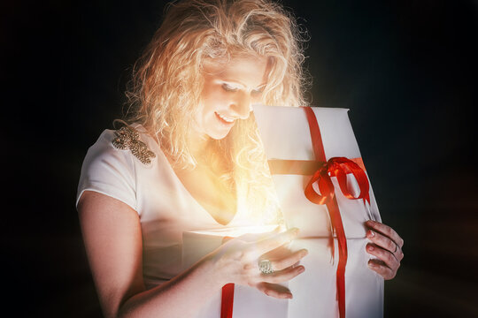 beautiful young woman opening gift box . isolated on black