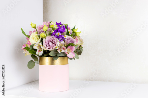 Beautiful bouquet of flowers in pink round box on a white table. Gift for holiday, birthday, Wedding, Mother's Day, Valentine's day, Women's Day. Floral arrangement in a hat box.