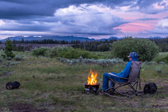 A Camper Man sitting on a camping rocking chair by a fire ring with views of distance mountains and dramatic clouds over fields with grass, shrub and forest, Yellowstone National Park, Montana