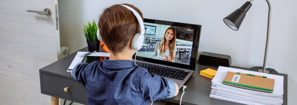 Unrecognizable boy with headphones receiving class at home with laptop from his bedroom. Home schooling concept