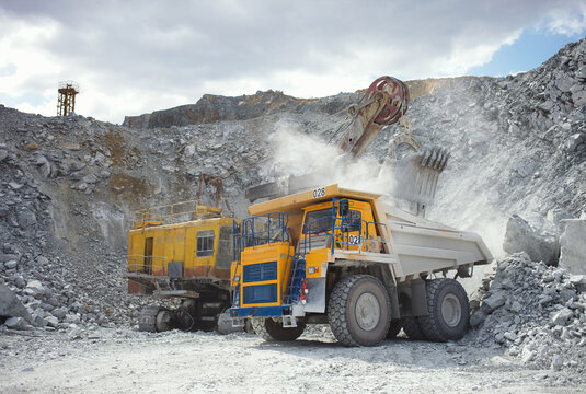 Heavy mining dump truck at the time of loading the large stone fragments in a limestone quarry, close-up.