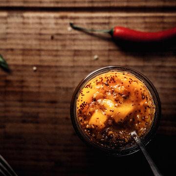 Mango Chutney in einem Glas und Löffel auf einem Holzbrett stehend, im Hintergrund frischer Chili.