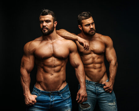 Two hunks standing at black background