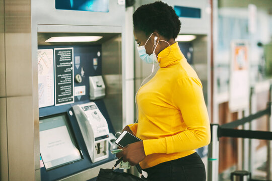 Dubai, UAE, November 2020 African woman wearing a protective mask withdraws money from a bank card at an ATM
