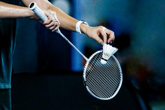 holding a white badminton racket ready to hit the ball