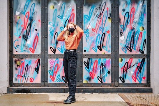 Girl wearing COVID-19 mask is posing full length by graffiti in Manhattan, New York. She is wearing black Dr. Martens boots, black military pants and dark orange knitted sweater. looking at camera.