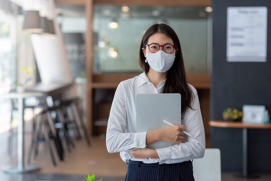 Asian business woman wear a mask to prevent COVID-19 at the office.