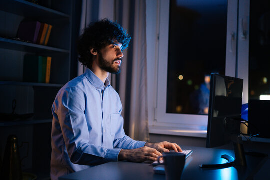 Side view of young freelancer working on computer and typing text on wireless keyboard while sitting at desk at home office workplace at late night in dark room. Concept of remote working.
