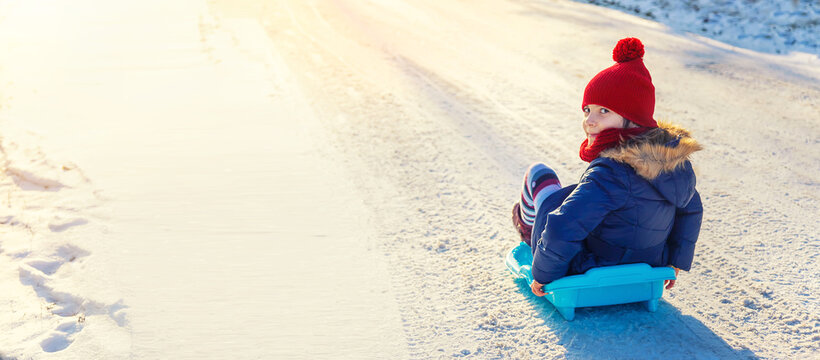 A child girl slides down a hill in the snow. Selective focus.
