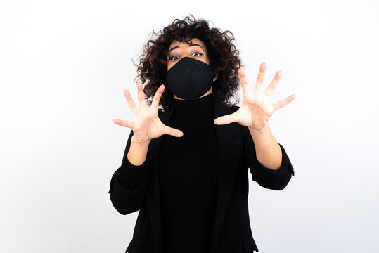 Dissatisfied young beautiful caucasian woman wearing medical mask standing against white wall, frowns face, has disgusting expression, shows tongue, expresses non compliance, irritated with somebody.