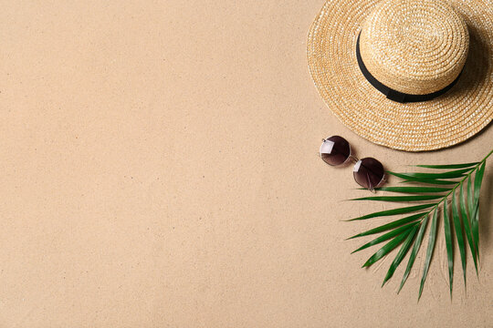 Straw hat, sunglasses, palm leaf and space for text on beach sand, flat lay. Summer vacation