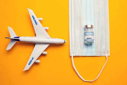Travel during covid-19 pandemic. Airplane model, protection medical mask, vaccine on yellow background.