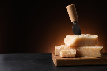 Delicious parmesan cheese with knife on black table. Space for text